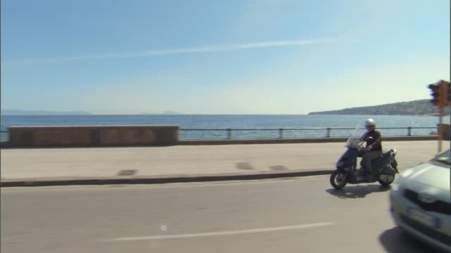 ws pan motorcycle driving down coastal highway in naples / naples, campania, italy - motorino video stock e b–roll