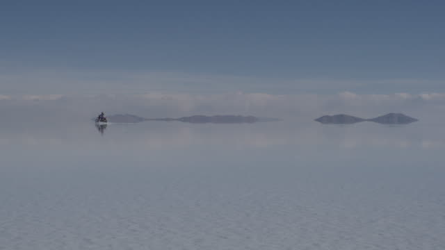 motorcycle driving through water on salar de uyuni (uyuni salt flat) / potosi, bolivia - horizon over land stock videos & royalty-free footage