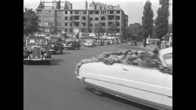 motorcycle escorts motorcade with joan fontaine's convertible draped with flowers driving though berlin / pov fontaine riding with festival director... - 1951 bildbanksvideor och videomaterial från bakom kulisserna