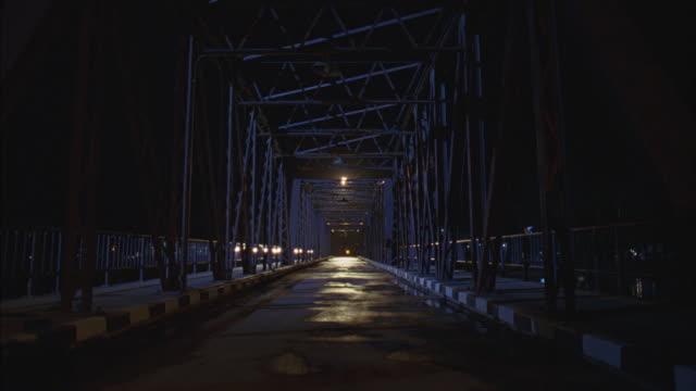 a motorcycle gang rides across a bridge at night. - biker gang stock videos & royalty-free footage