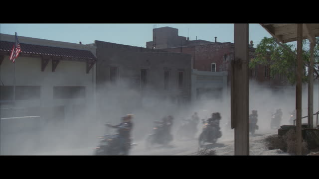ms, pan, motorcycle gang riding through small western rural town, usa - biker gang stock videos & royalty-free footage