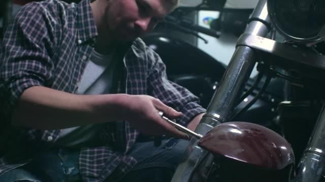 Motorcycle mechanic loosing a fender bolt