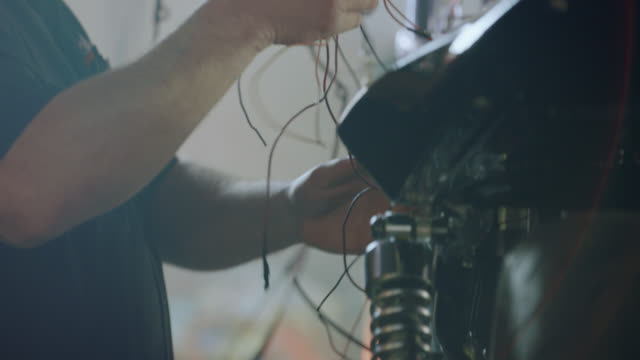 CU. Motorcycle mechanic works with a tangle of wires in auto repair shop.