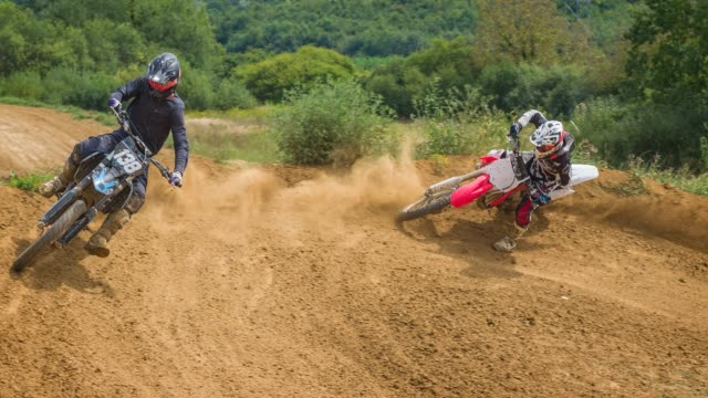 stockvideo's en b-roll-footage met motorfiets off road racing, motocross rijders concurreren op dirt track - valhelm