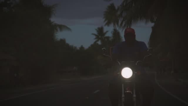 暗い島道のオートバイ。 - ヘッドランプ点の映像素材/bロール