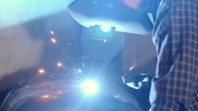 Motorcycle repairman using a welding torch