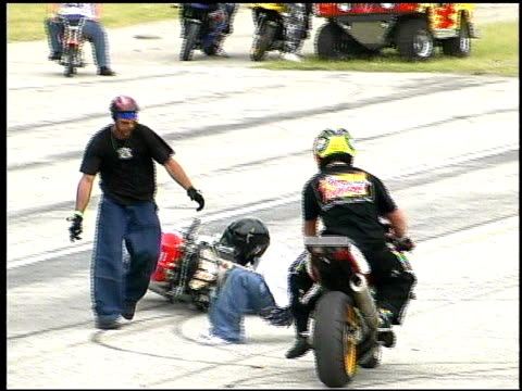 / motorcycle rider on speedway showing off stunt sitting with feet over handlebars loses control of bike and crashes / rider gets up limping at first...