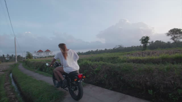 motorcycle riding man and woman couple on road in exotic tropical bali, indonesia. - slow motion - bali stock videos & royalty-free footage
