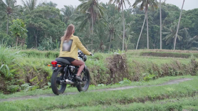motorcycle riding woman in exotic tropical bali, indonesia. - slow motion - bali stock videos & royalty-free footage