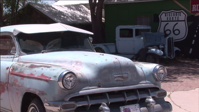 a motorcycle sits on a trailer next to an old car. - weathered stock videos & royalty-free footage
