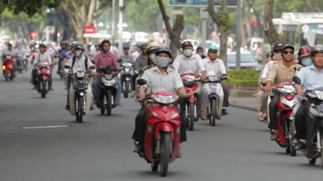 ws ld motorcycle traffic along busy street / vietnam - crash helmet stock videos & royalty-free footage