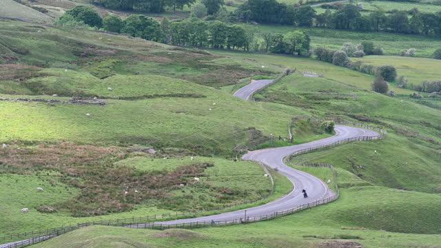 motorcycle travelling up winding country road in peak district - resmål bildbanksvideor och videomaterial från bakom kulisserna
