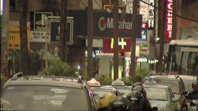 ms motorcycles and cars passing through city street / bali, indonesia - västerländsk text bildbanksvideor och videomaterial från bakom kulisserna