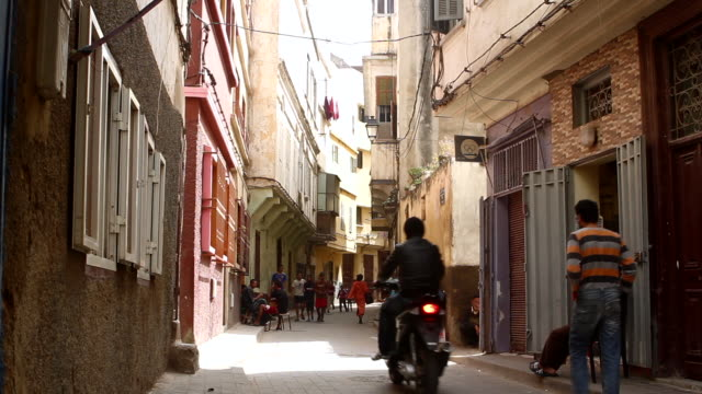 motorcycles and pedestrians pass by on a street in casablanca. - old town stock videos & royalty-free footage