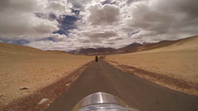 pov motorcycles driving through dry desert landscape under a bright blue sky with fluffy white clouds in leh, india - royal blue stock videos & royalty-free footage