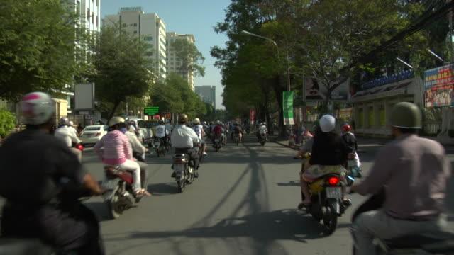 vídeos de stock, filmes e b-roll de pov motorcycles on busy city street / ho chi minh city, vietnam - artigo de vestuário para cabeça