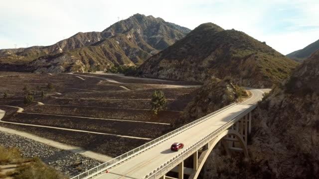 モーターサイク リストと車ですれ違うリトルタジャンガキャニオン ダム橋-空中ドローンを撮影 - エンジェルス国有林点の映像素材/bロール