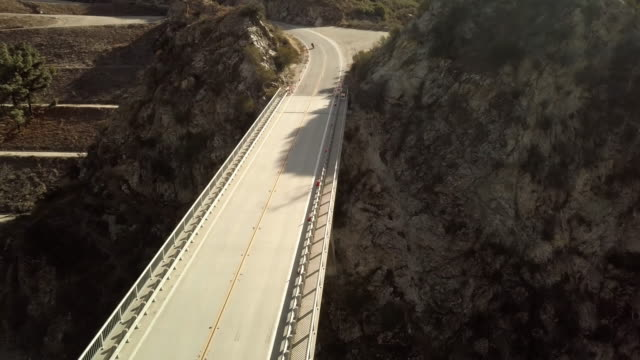 モーターサイク リスト リトルタジャンガキャニオン ダム橋-空中ドローン ショットで運転 - エンジェルス国有林点の映像素材/bロール