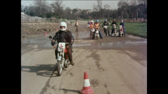 MONTAGE Motorcyclist practice riding around safety cones / United Kingdom
