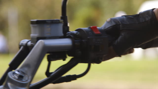 Motorcyclist revs motorcycle engine.