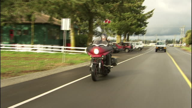 a motorcyclist rides a motorcycle with his american eskimo dog. - american eskimo dog stock videos & royalty-free footage