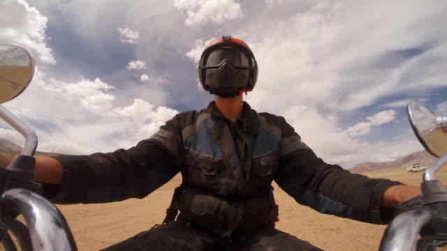 vídeos y material grabado en eventos de stock de motorcyclist riding sandy surface of wide valley floor in the himalayas - manillar