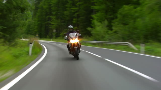 stockvideo's en b-roll-footage met motorcyclist riding towards camera on cloudy day - tweebaansweg