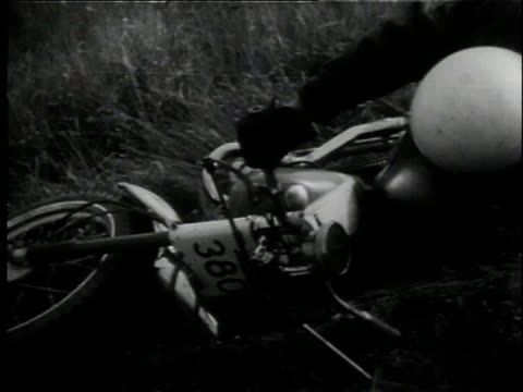 vidéos et rushes de 1958 ts motorcyclist sliding onto his side during all-terrain race, then getting up, straightening out the bike, and going on again / lansing, michigan, united states - lansing