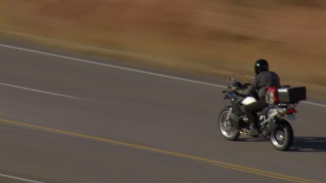 A motorcyclist travels on a desert highway.