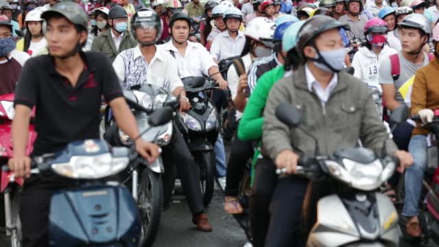 vídeos de stock e filmes b-roll de cu motorcyclists at traffic light - capacete moto