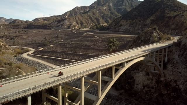 motorcyclists driving on the tujunga dam bridge- aerial drone shot - motorcycle racing stock videos and b-roll footage