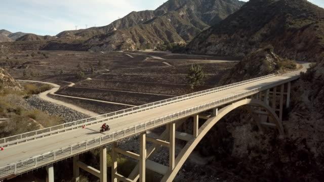バイク運転リトルタジャンガキャニオン ダム橋-空中にドローン ショット - エンジェルス国有林点の映像素材/bロール