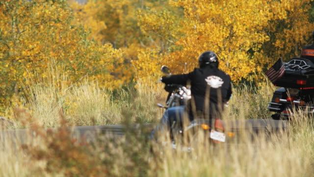 vídeos de stock e filmes b-roll de motorcyclists going around a bend - capacete moto