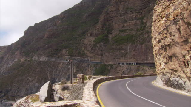 Motorcyclists ride along a coastal highway next to Hout Bay. Available in HD