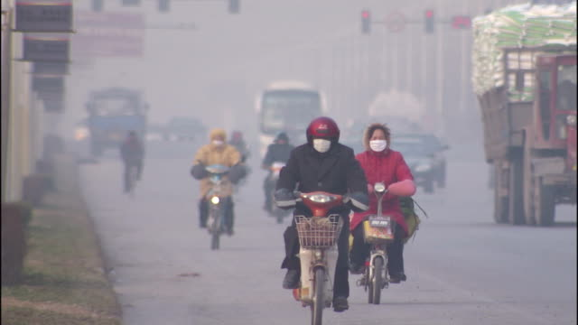 motorcyclists wear face masks as they commute on a smoggy street. - luftverschmutzung stock-videos und b-roll-filmmaterial