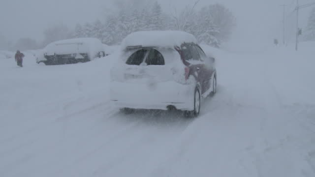 a motorist navigates snow covered roads and near zero visibility in adams new york during a heavy lake effect snowstorm - scott mcpartland stock videos & royalty-free footage