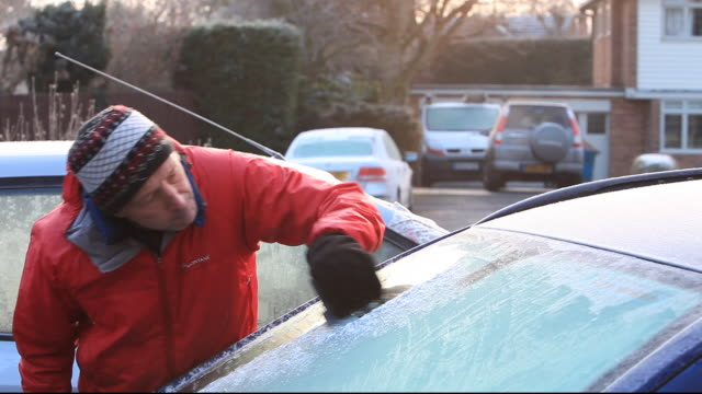 A motorist scraping frost off a cars windows.