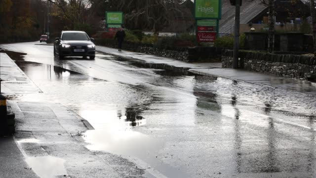 motorists driving too fast through large puddles soaking pedestrians and property in ambleside, cumbria, uk. - splashing stock videos & royalty-free footage