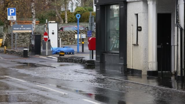 motorists driving too fast through large puddles soaking pedestrians and property in ambleside, cumbria, uk. - spray stock videos & royalty-free footage
