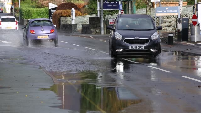 motorists driving too fast through large puddles soaking pedestrians and property in ambleside, cumbria, uk. - wet stock videos & royalty-free footage