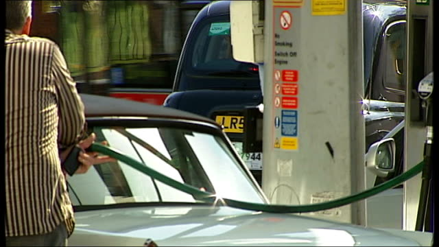 Motorists filling cars at petrol station ENGLAND London EXT Various shots of car drivers filling up cars with fuel in Texaco petrol station forecourt...