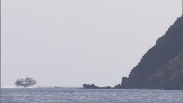 a motorized boat approaches a rocky shoreline. - herumfahren stock-videos und b-roll-filmmaterial