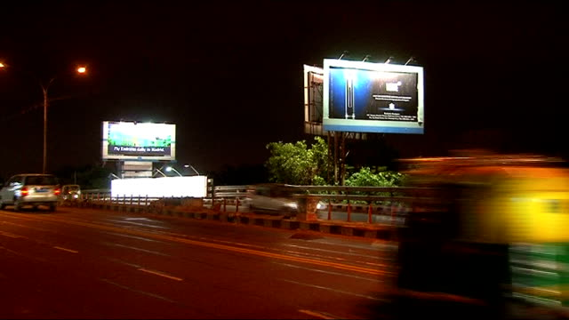 Delhi Various shots of illuminated advertising billboards alongside motorway advertising luxury products including Breitling watches Hilton Hotel...