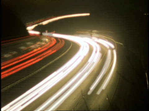 vidéos et rushes de t/l motorway at night, m40 oxford - streaky traffic rushing around s-shaped bend in both directions (driving on left hand side of road) - phare de véhicule