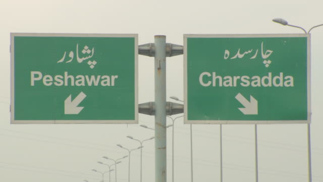 Freeway freestanding bilingual direction signs Peshawar arrow left Chsradda arrow right TD WS Access road w/some traffic passing people walking in...