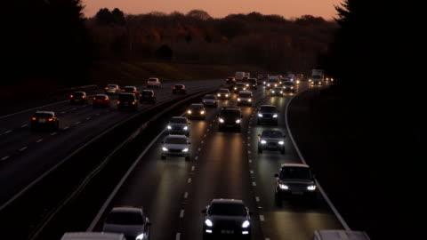 autobahnverkehr in der dämmerung, autos mit scheinwerfern. - vereinigtes königreich stock-videos und b-roll-filmmaterial