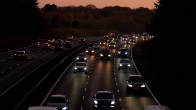 motorway traffic driving at dusk, cars with headlights. - kent england stock videos & royalty-free footage