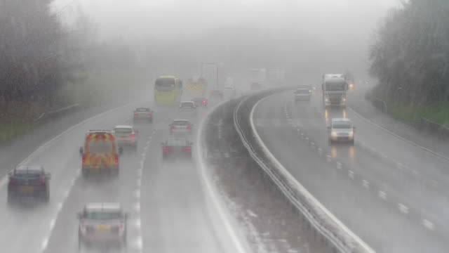 motorway traffic driving in hazardous sleet. - shower stock videos & royalty-free footage