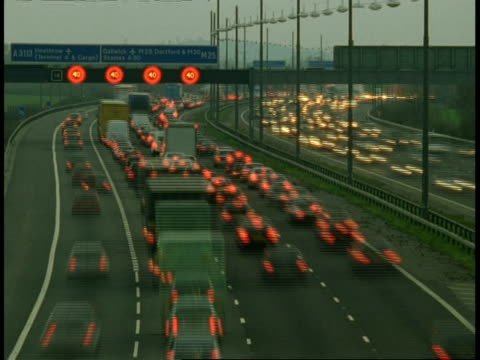 t/l motorway traffic, m25 near heathrow airport - daylight changes to night-time, traffic builds up and then clears - m25 video stock e b–roll