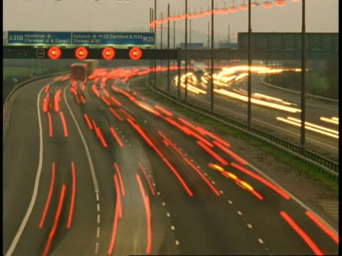 T/L Motorway Traffic, M25 near Heathrow Airport - daylight changes to night-time, streaky traffic builds up